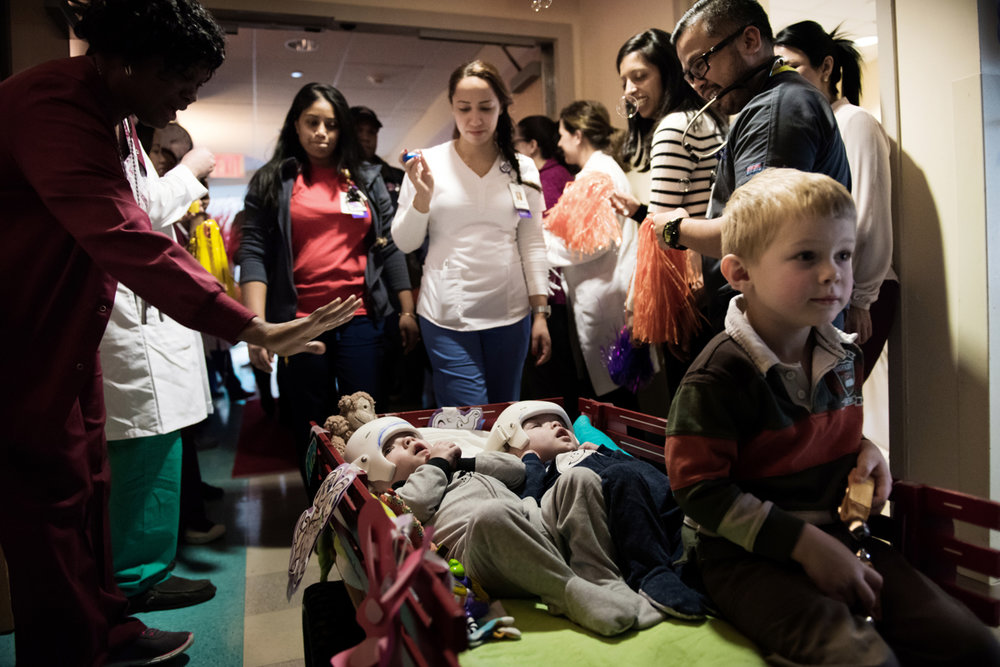 Jadon (left) and Anias McDonald look up PICU staff as they leave their hospital room at Montefiore Children's Hospital in The Bronx, New York, N.Y. on December 14, 2016.