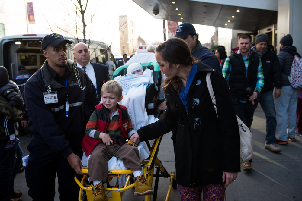 Nicole McDonald holds her eldest son Aza's hand as he cries while riding on the stretcher holding his younger brother Jadon while they leave Montefiore Children's Hospital in The Bronx, New York, N.Y. on December 14, 2016.