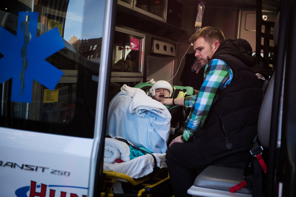 Christian McDonald looks on anxiously as his son Anias cries after being loaded into an ambulance to leave Montefiore Children's Hospital in The Bronx, New York, N.Y. on December 14, 2016.