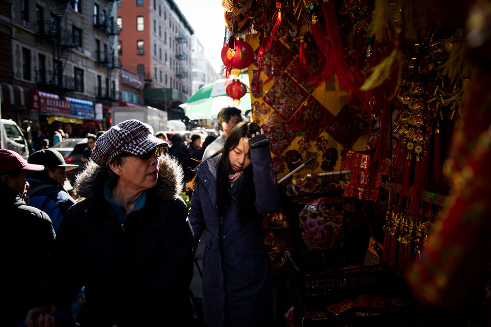 A woman passes a stand selling lanterns and other items in preparation for Chinese New Year in the Chinatown neighborhood of Manhattan in New York, NY.