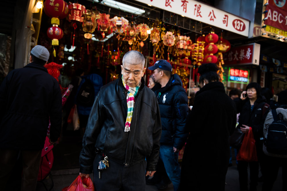A man pauses before crossing the street outside a store in the Chinatown neighborhood of Manhattan in New York, NY.