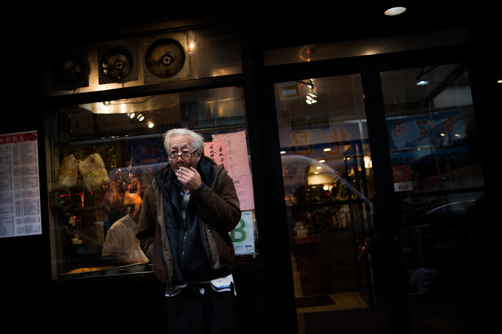 An elderly man smokes a cigarette outside a restaurant in Chinatown neighborhood of Manhattan in New York, NY.