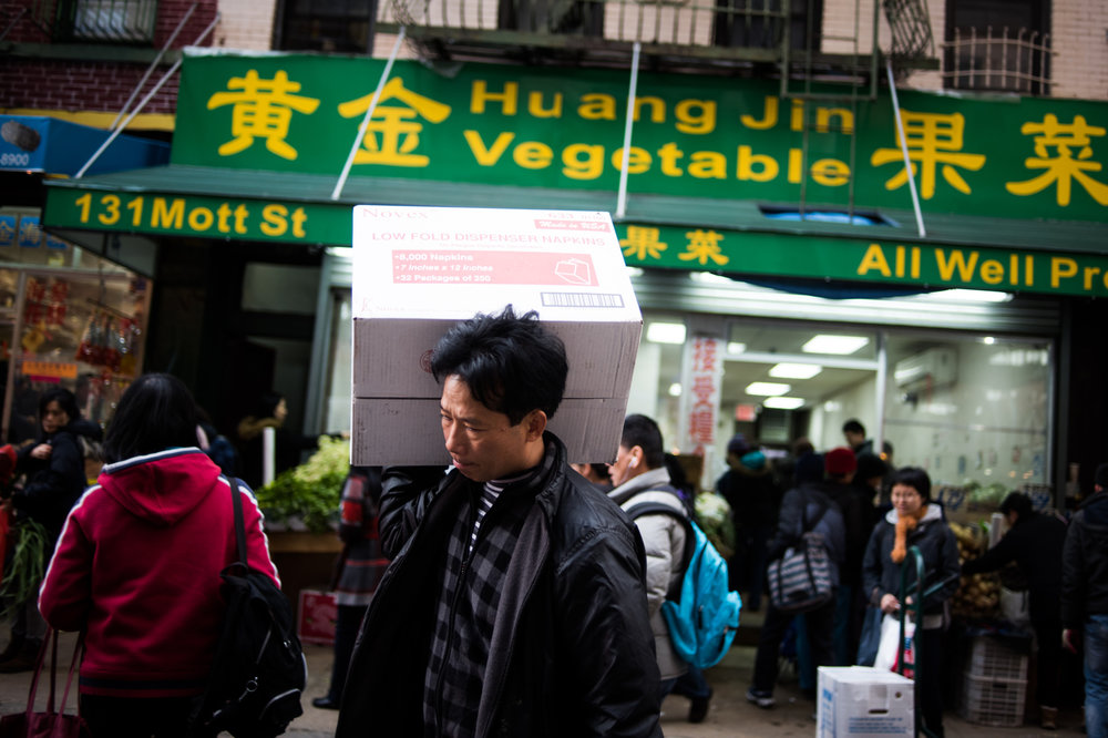 A man carries a box of produce across the street in the Chinatown, New York, NY.