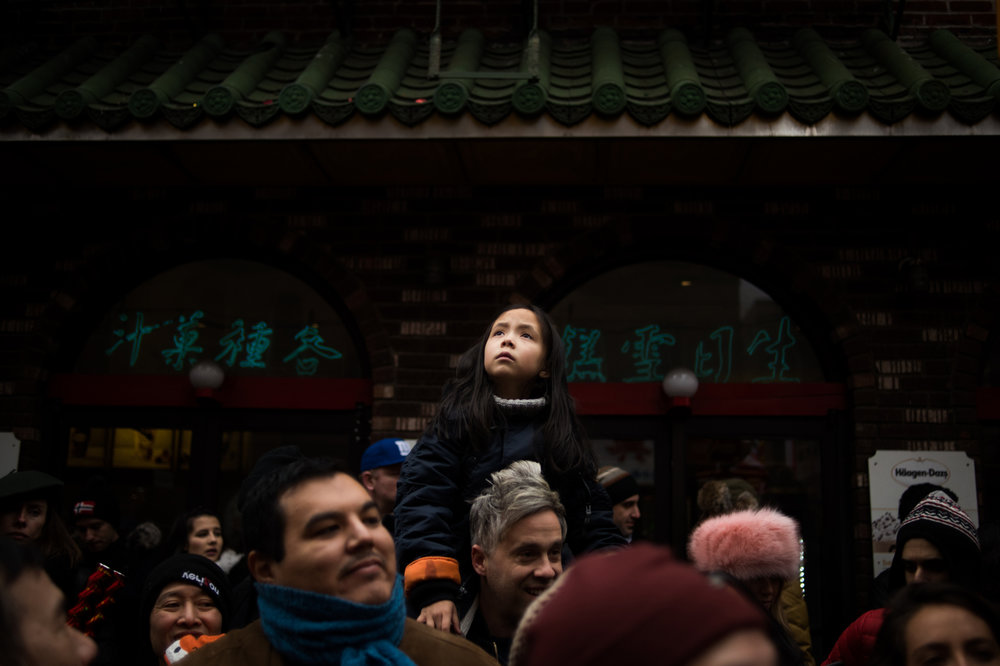 A young girl watches floating confetti from party poppers set off during the Chinese New Year Parade in the Chinatown neighborhood of New York.
