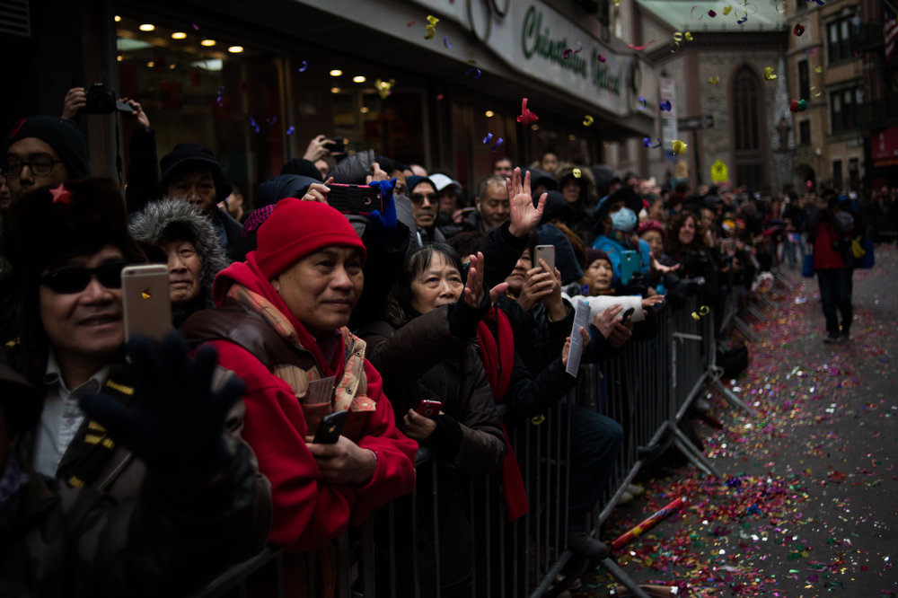 People reach out for falling confetti during the Chinese New Year Parade in the Chinatown neighborhood of New York.