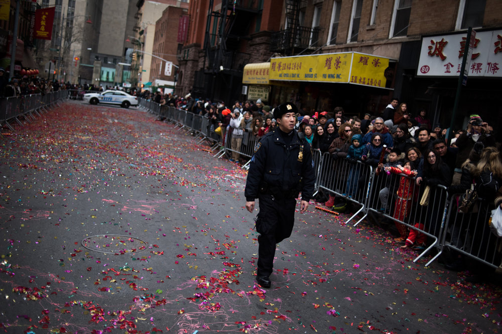 A Chinese-American police officer walks down a street emptied after floats departed for the Chinese New Year Parade in the Chinatown neighborhood of New York.