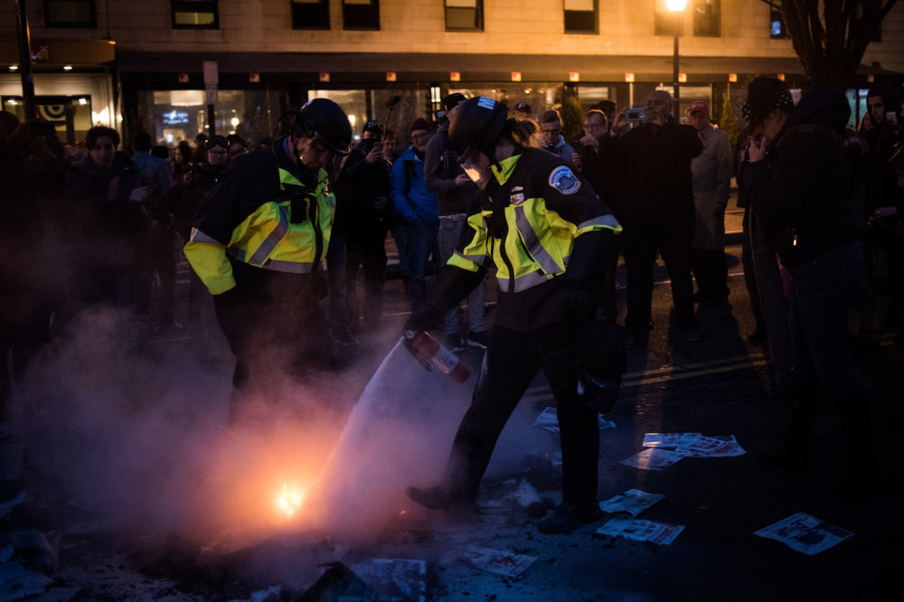 Police officers put out a fire started during protests against Donald Trump's inauguration as the 45th President of the United States in Washington, D.C., on January 20, 2017. Credit: Mark Kauzlarich for CNN