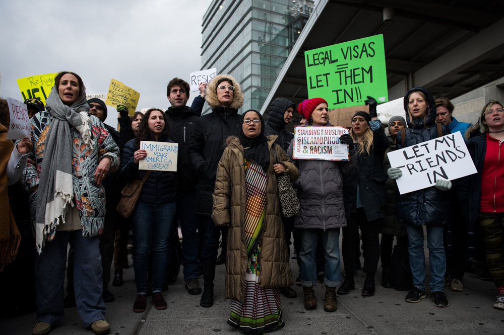 Kazi Fouzia, center, a green card holder who left Bangladesh for the United States 10 years ago, stands with protestors at a parking lot outside John F. Kennedy International Airport in New York, NY on Saturday, January 28, 2017. Credit: Mark Kauzlarich for CNN