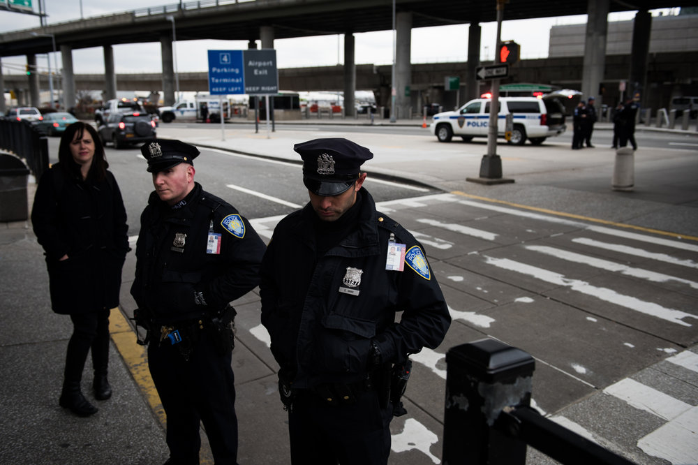 Port Authority Police Officers guard a walkway near protestors outside John F. Kennedy International Airport surrounded by  in New York, NY on Saturday, January 28, 2017. Credit: Mark Kauzlarich for CNN