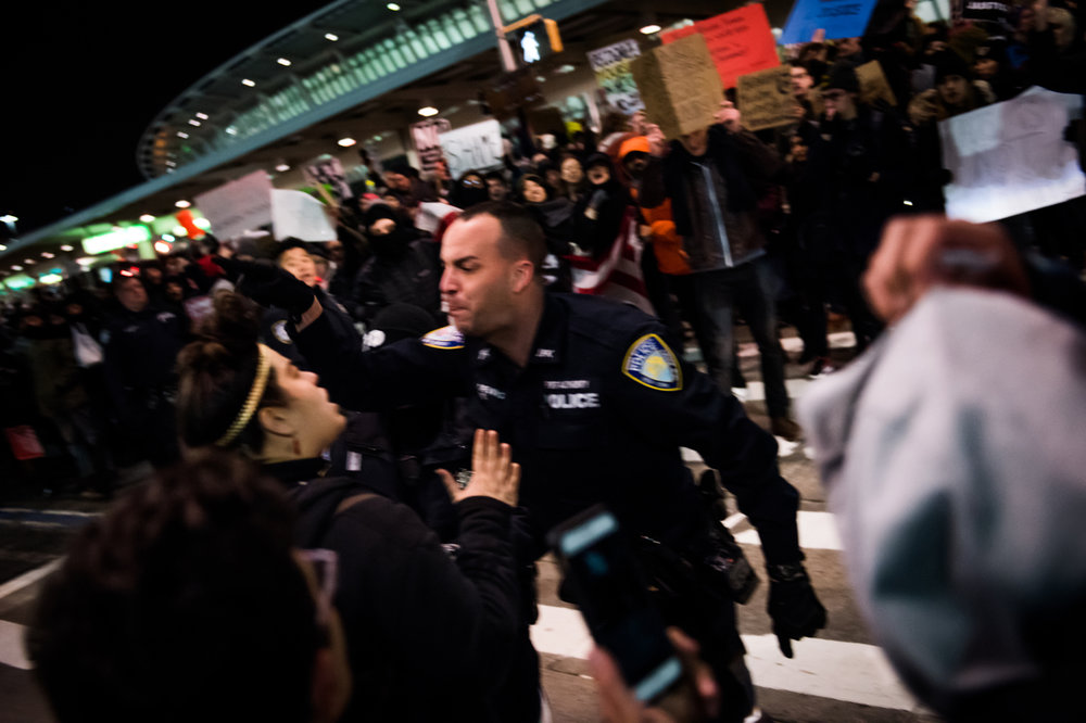 A Port Authority police officer screams at a protestor at John F. Kennedy International Airport in New York, NY on Saturday, January 28, 2017. Credit: Mark Kauzlarich for CNN