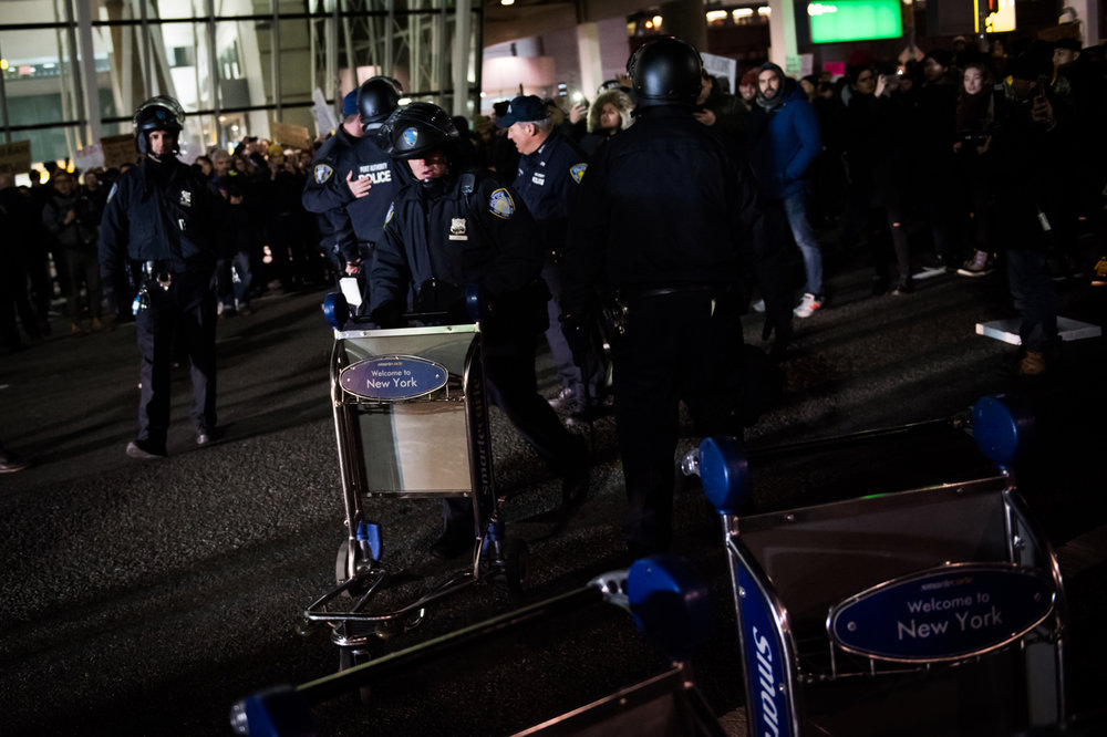 Police Authority police move carts used by protestors as barricades at John F. Kennedy International Airport in New York, NY on Saturday, January 28, 2017. Credit: Mark Kauzlarich for CNN