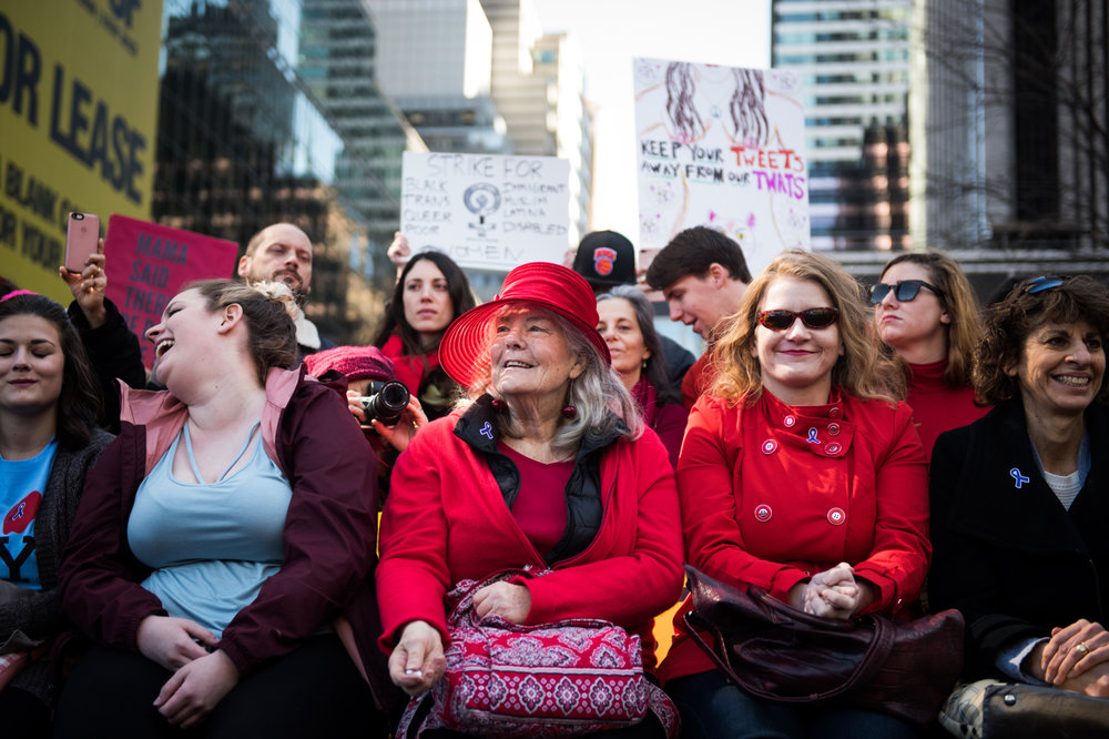 Women sit along the side of a sidewalk during an International Women's Day rally and march in New York, NY on March 8, 2017. CREDIT: Mark Kauzlarich for CNN