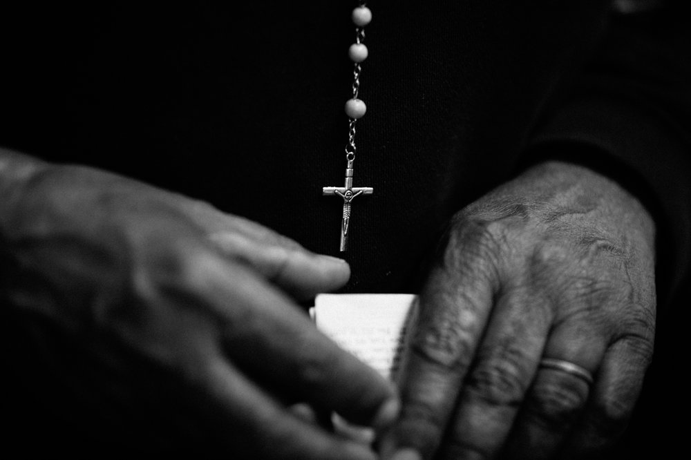A woman from the Dominican Republic holds business cards and notes from lawyers in front of her rosary as she waits to speak with a lawyer at Catholic Charities Community Services walk in legal aid service in New York, NY on March 9, 2017. CREDIT: Mark Kauzlarich for CNN