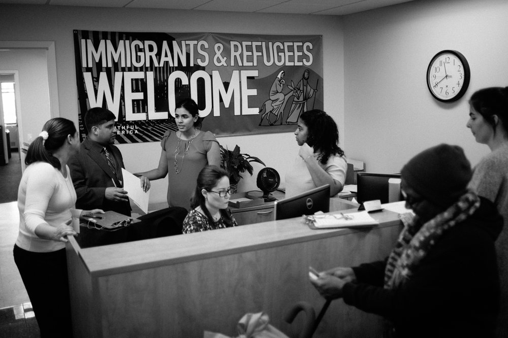 Staff with Catholic Charities Community Services speak with people waiting to talk to lawyers about immigration relations issues in New York, NY on March 9, 2017. CREDIT: Mark Kauzlarich for CNN