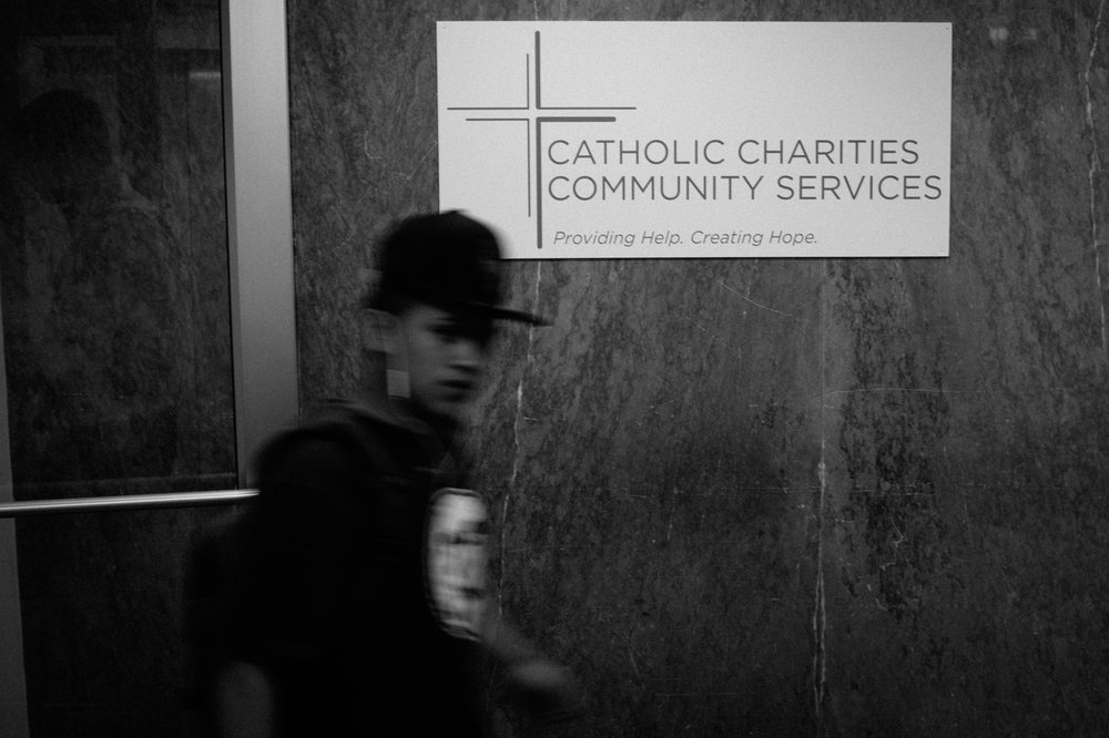 A young man walks past a sign for Catholic Charities Community Services during one of their walk-in periods for legal aid related to immigration issues in New York, NY on March 9, 2017. CREDIT: Mark Kauzlarich for CNN