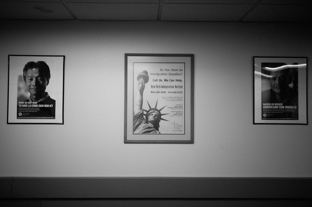 Signs welcoming immigrants and offering guidance hang on the wall at Catholic Charities Community Services offices in New York, NY on March 9, 2017. CREDIT: Mark Kauzlarich for CNN