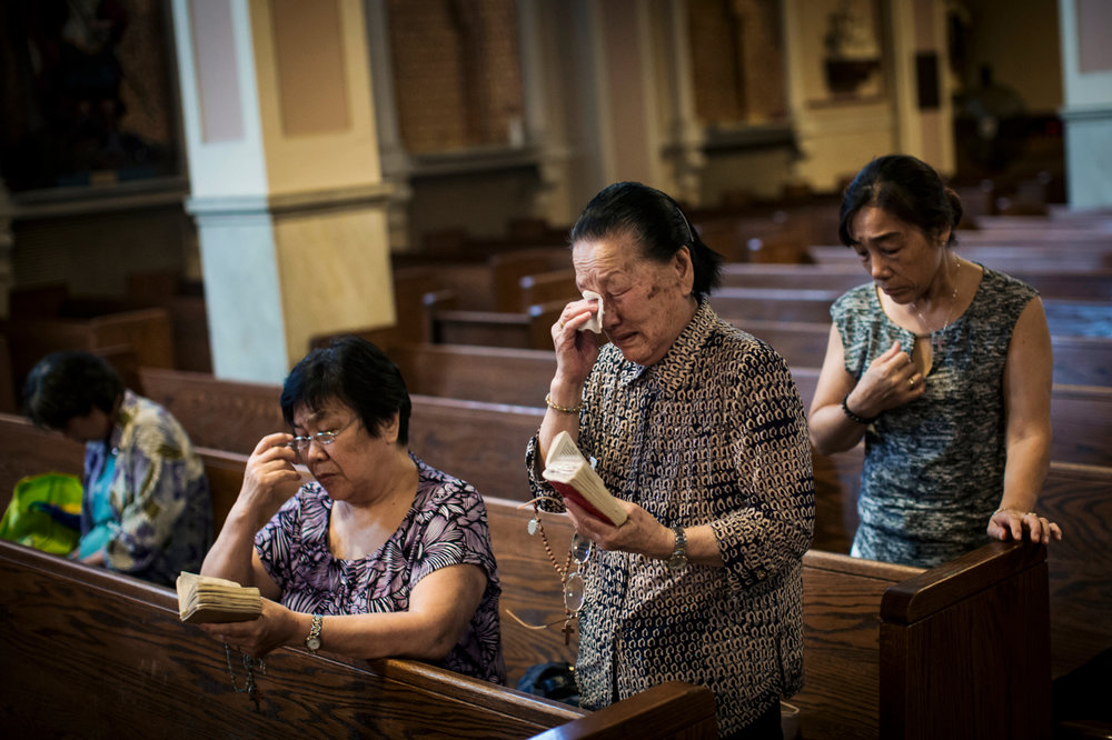 Chen Yizhu wipes away tears while praying after morning mass and before late morning Mandarin mass at St. Joseph church in Chinatown, during it's last day on Friday, July 31, 2015.