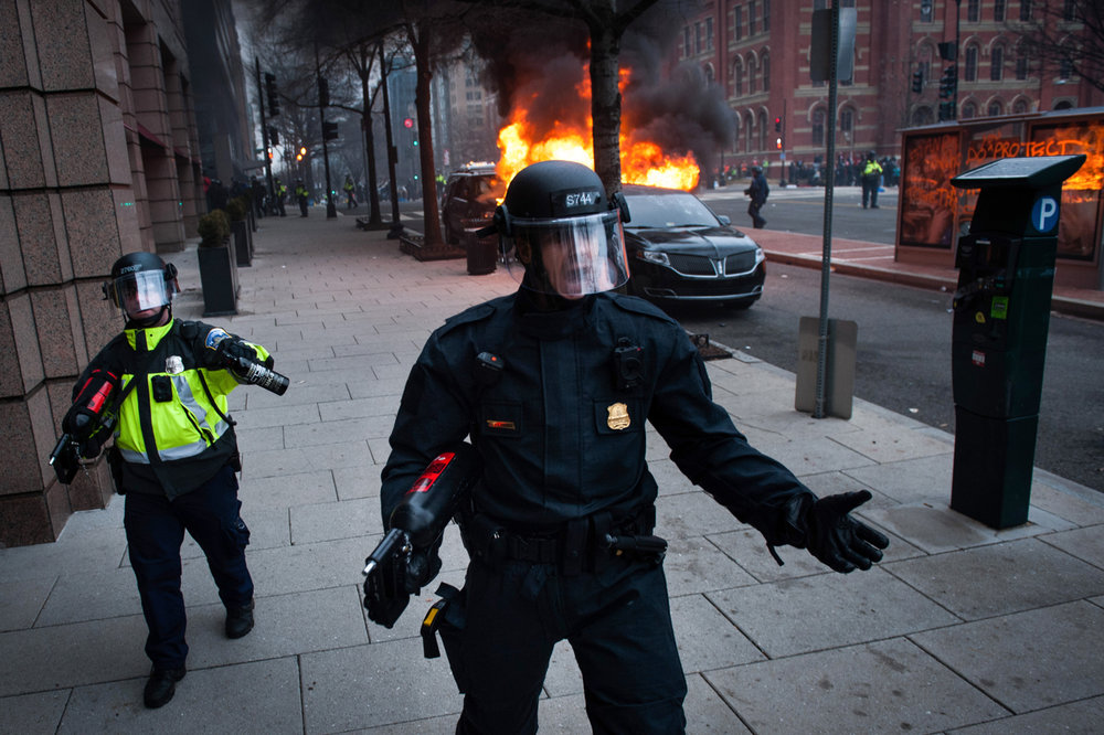 Washington Metro Police use water canons and pepper spray to move protestors away from a burning limousine, lit on fire by ANTIFA protesters, on the day of the President Donald Trump's inauguration in Washington, D.C., on January 20, 2017.