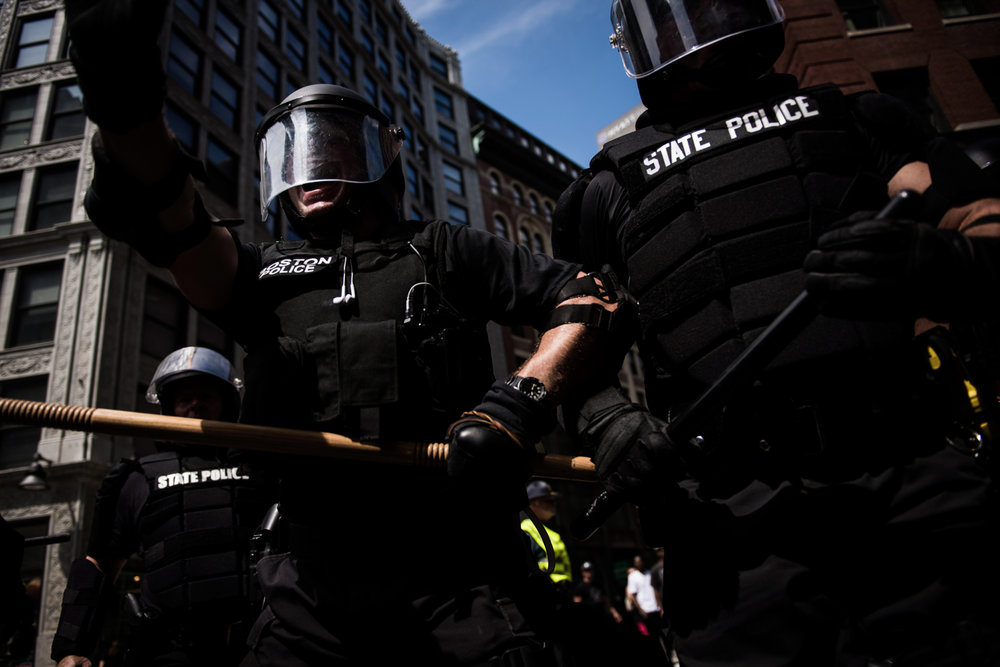 Boston Police and Massachusetts State officers in riot gear yell at a crowd as people are shoved and tackled by police while escorting police wagons full of free-speech rally-goers away from Boston Common in Boston, MA on Saturday, August 19, 2017.