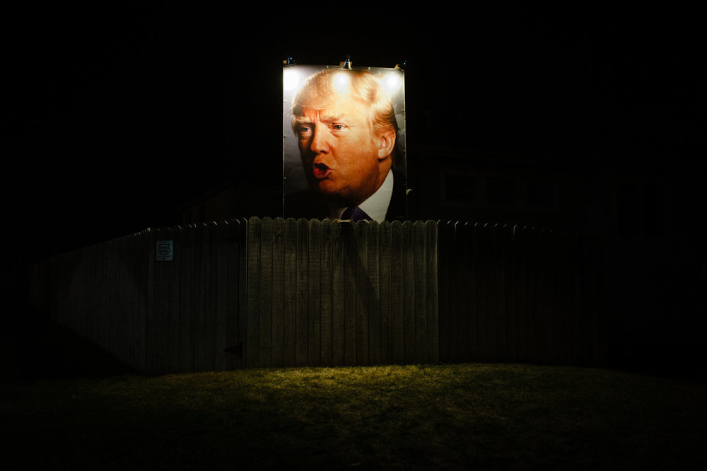 A photo of U.S. Republican presidential candidate Donald Trump stands over the fence at the home of George Davey, a formerly registered independent turned Republican Trump supporter. Davey puts up signage every election at his home off Jordan Creek Parkway and Pommel Place in Des Moines, IA.