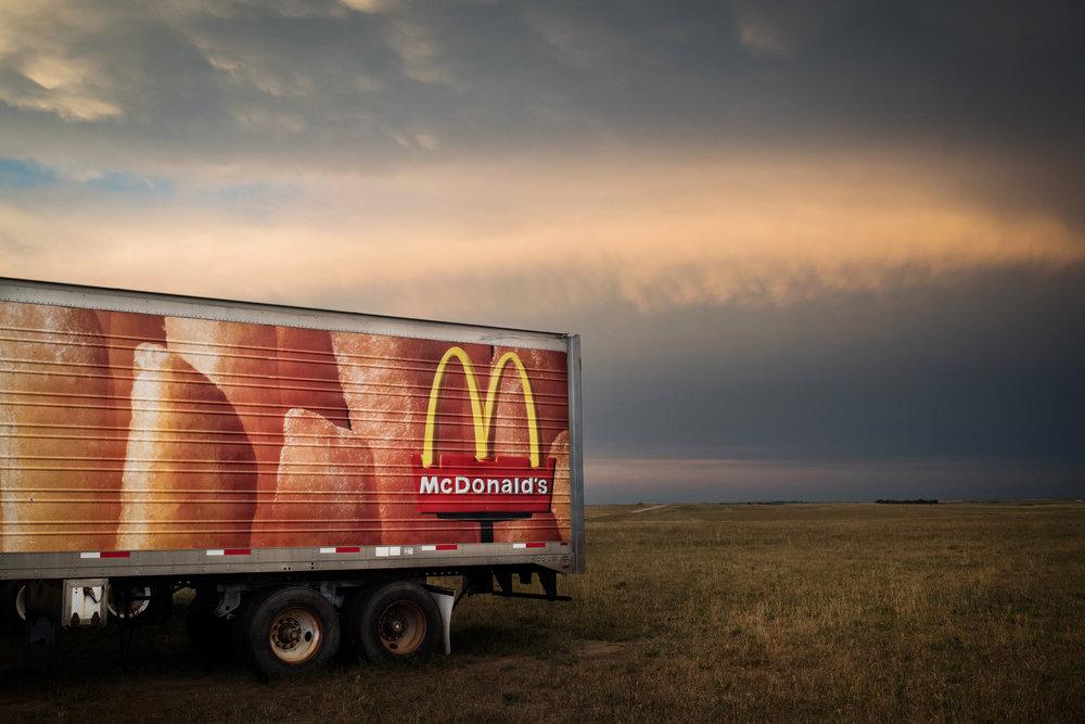 """45º31'48.6""""N, 102º48'17.6""""W. 107 miles from the nearest McDonald's.  A McDonalds trailer sits in a field outside in the small town of Prairie City, SD on July 31, 2017. Not far from the former McFarthest point in America, a local rancher bought two semi trailers for storage and left them in a field, one of which now acts as a reminder of the ubiquitous nature of corporate America."""