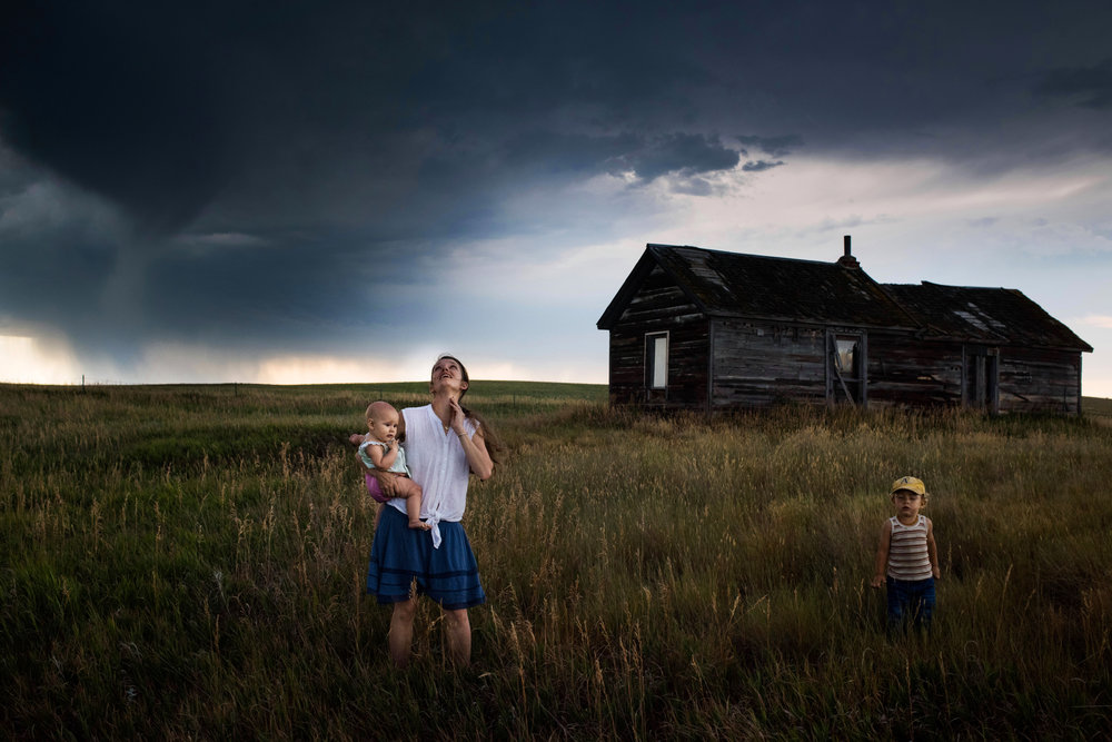 """45º33'14.2""""N, 102º30'36.1""""W. 114 miles from the nearest McDonald's.  Eliza Blue holds her daughter Emmy as her son Wesley closes his eyes and feels the coming storm winds on his face as they stand near an abandoned farmhouse on their leased land in Bison, SD. Ranchers and farmers have spent much of the droughty summer watching clouds on the horizon, hoping storms would hit, but most pass by without rain."""