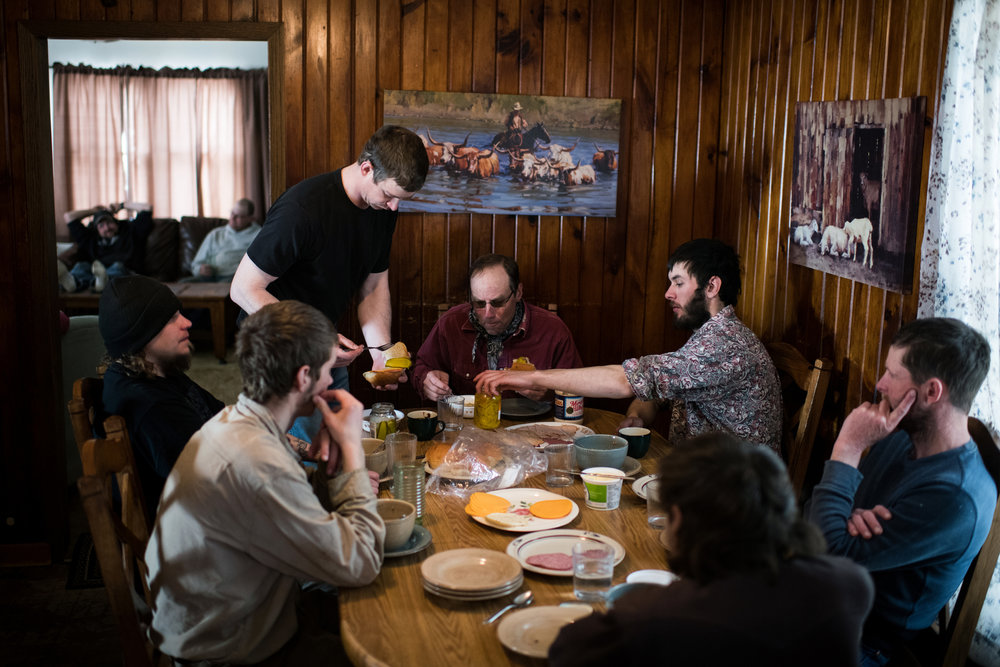 """45º29'43.2""""N, 102º19'59.6""""W. 120 miles from the nearest McDonald's.  A group of men sit down around the dinner table for a meal of soup and sandwiches as they take a break from shearing sheep in the 20 degree weather and substantial winds at the Kronberg ranch in Meadow, SD on April 7, 2018. Sheep need to be sheared yearly for their health, but the cold weather caused issues, forcing the delay of shearing some of the herd, putting the rest in a barn, but for all the work, wool is worth hardly any money to working ranchers."""