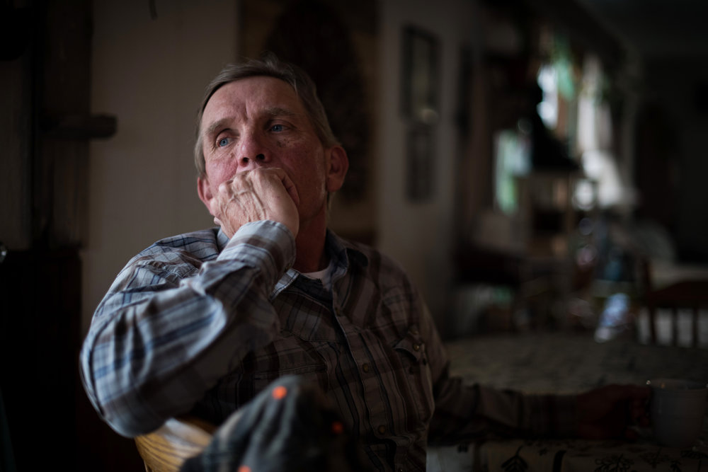 """45º32'31.3""""N, 102º29'52.1""""W. 110 miles from the nearest McDonald's.  Sion Hanson sits in a neighbor's home and drinks coffee before dinner in Bison, SD on April 6, 2018. A maintenance worker for the city of Bison, he used to wake up every morning early to drink coffee, smoke a cigarette, and play cribbage online, playing over 35,000 games on Yahoo, but at almost 60 years old, he still dreams of owning a small ranch with a herd of bison."""