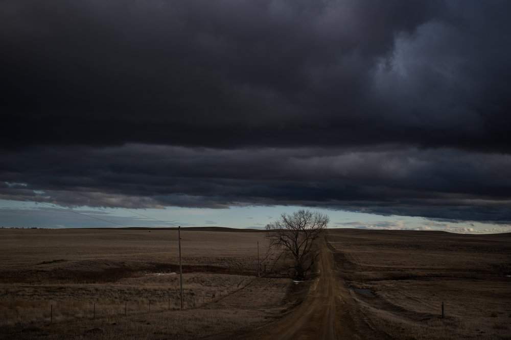 """45º20'46.8""""N, 101º42'41.4""""W. 141 miles from the nearest McDonald's.  Stormy clouds hang over a dirt road in Isabel, SD on April 11, 2018. Even with a pickup and four-wheel drive, such roads quickly become impassable when storms can dump 10 inches of snow and 50+ mph wind gusts are common, as they were when winter storm Evelyn hit on April 12, 2018."""