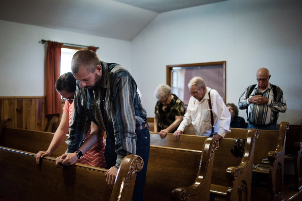 """45º26'49.9""""N, 102º10'07.6""""W. 127 miles from the nearest McDonald's.  Parishioners pray while worshiping at Coal Springs church in Meadow, SD. While many old prairie churches have closed over the years, many other small congregations still struggle to survive, or have multi-point parishes with one pastor serving a large area."""