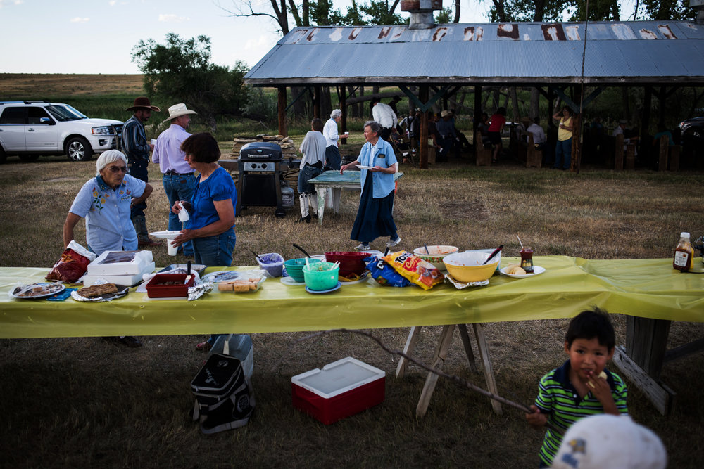 """45º27'04.3""""N, 102º02'27.5""""W. Exactly 134 miles from two separate McDonald's.  People mill about at a potluck before a Ranchers Camp worship service in a field between the towns of in Meadow and Glad Valley, SD on July 30, 2017."""