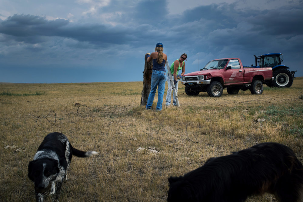 """45º18'57.2""""N, 102º11'54.2""""W. 120 miles from the nearest McDonald's.  Jamie Hepper and her 14-year-old daughter Aiyana Byrd work on removing fencing around an old hay yard on their ranch south of Meadow, SD. Jamie, a single mother, is one of the only local female ranchers working almost entirely alone, save for the help of her daughter."""