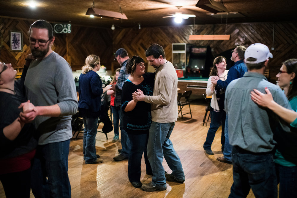 """45º31'48.9""""N, 102º12'59.8""""W. 123 miles from the nearest McDonald's.  Couples practice the two-step during dance lessons at Smoky's Bar and Grill in Meadow, SD on April 8, 2018. Smoky's is the main social hub for the community year-round, run by a couple, Andrea Block and Shiloh Lorius, left, who returned to the area and bought the business and revitalized it after years of poor management for years and before that a 20-year closure due to an owner's arrest for drug trafficking."""