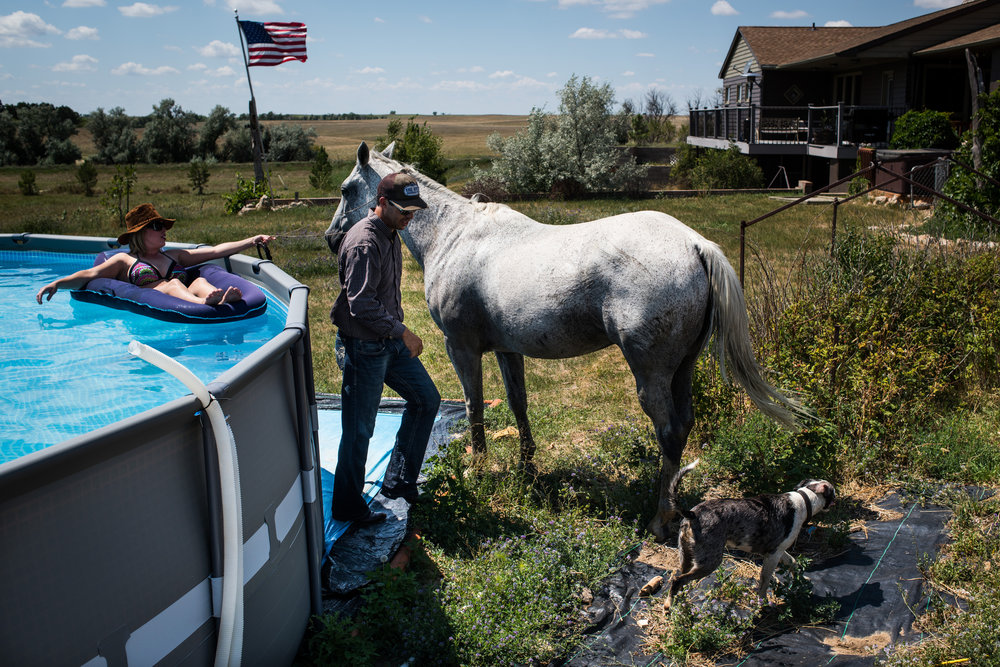 """45º30'35.5""""N, 102º13'48.2""""W. 124 miles from the nearest McDonald's.  Shane Yalowizer goes to get ready to swim as his girlfriend holds the war bridle on Fred the horse his ranch in Meadow, SD on July 28, 2017. South Dakota spent the summer in the midst of a state of emergency-level drought that caused many ranchers to sell parts of their herds to pay for feed and farmers to harvest their crops at a loss. Yalowizer works for the US Department of Agriculture's Natural Resources Conservation Service helping ranchers apply for funds to protect against drought or mitigate the disastrous results."""