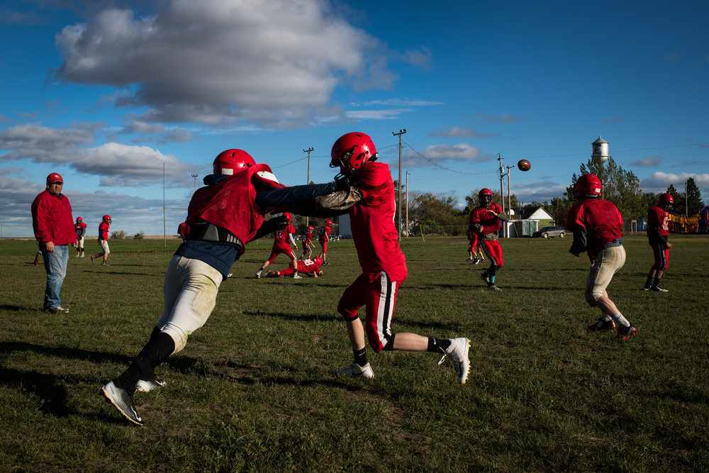 """45º31'30.5""""N, 102º27'48.7""""W. 124 miles from the nearest McDonald's.  Members of the Bison High School Cardinals varsity football team practice in Bison, SD. With only 46 students in the school, the team competes regionally in 9-man football, with 16-17 total players, many of whom, the coach said, only play varsity out of the team's necessity and not their personal ability."""