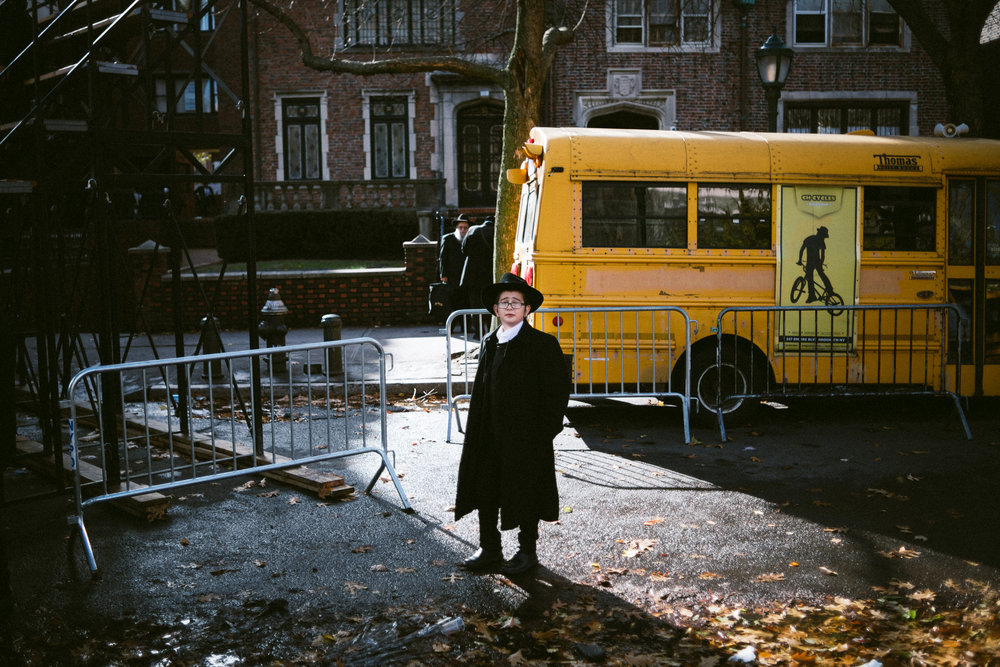 A young Chabad-Lubavitch boy, stands near a school bus after watching the a group photo of thousands in front of the movement's headquarters in the Crown Heights neighborhood of Brooklyn, NY.