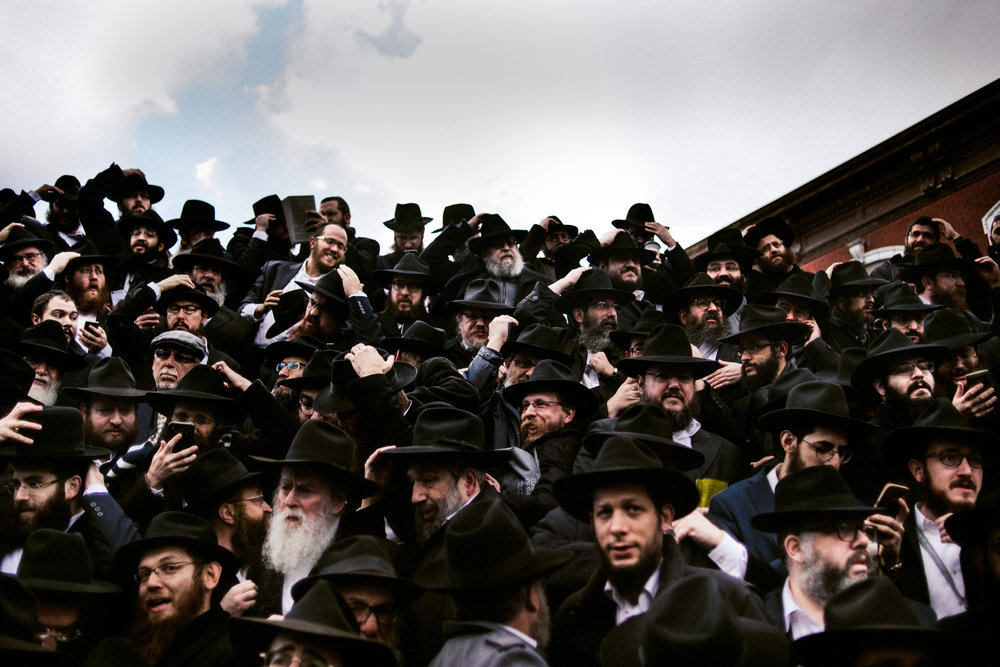 Chabad-Lubavitch rabbis hold on to their hats in a gust of wind as they gather for a group photo in front of the movement's headquarters in the Crown Heights neighborhood of Brooklyn, NY in 2017.
