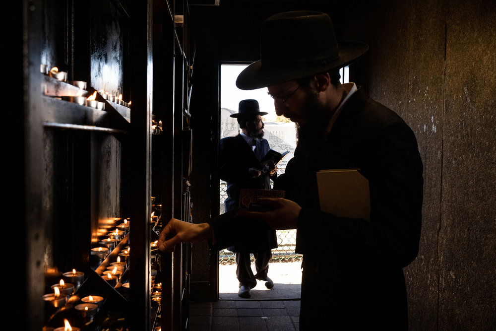 A Chabad-Lubavitch rabbi light candles as he prepares to pray at the Ohel, the gravesite of the Lubavitcher Rebbe Menachem M. Schneerson in Queens, NY.