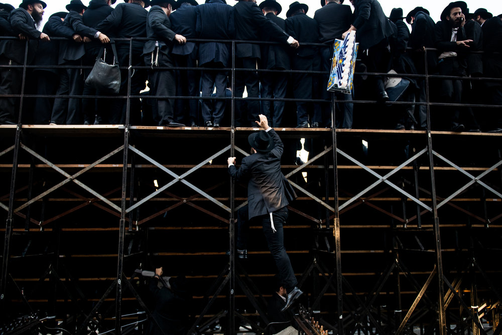 A Chabad-Lubavitch rabbi climbs the back of some stands as thousands gather for a group photo in front of the movement's headquarters in the Crown Heights neighborhood of Brooklyn, NY.