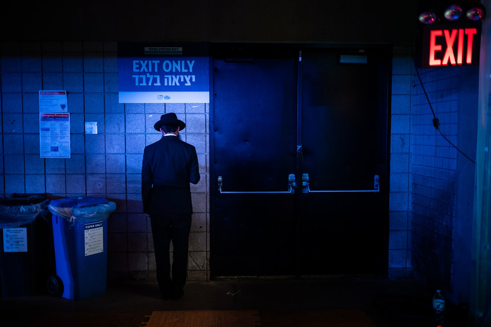 A Chabad-Lubavitch rabbi prays in a corner as thousands gather for a banquet in Suffern, NY. Each year, the International Conference of Chabad-Lubavitch Shluchim, or emissaries, takes place in the New York City area for six days.