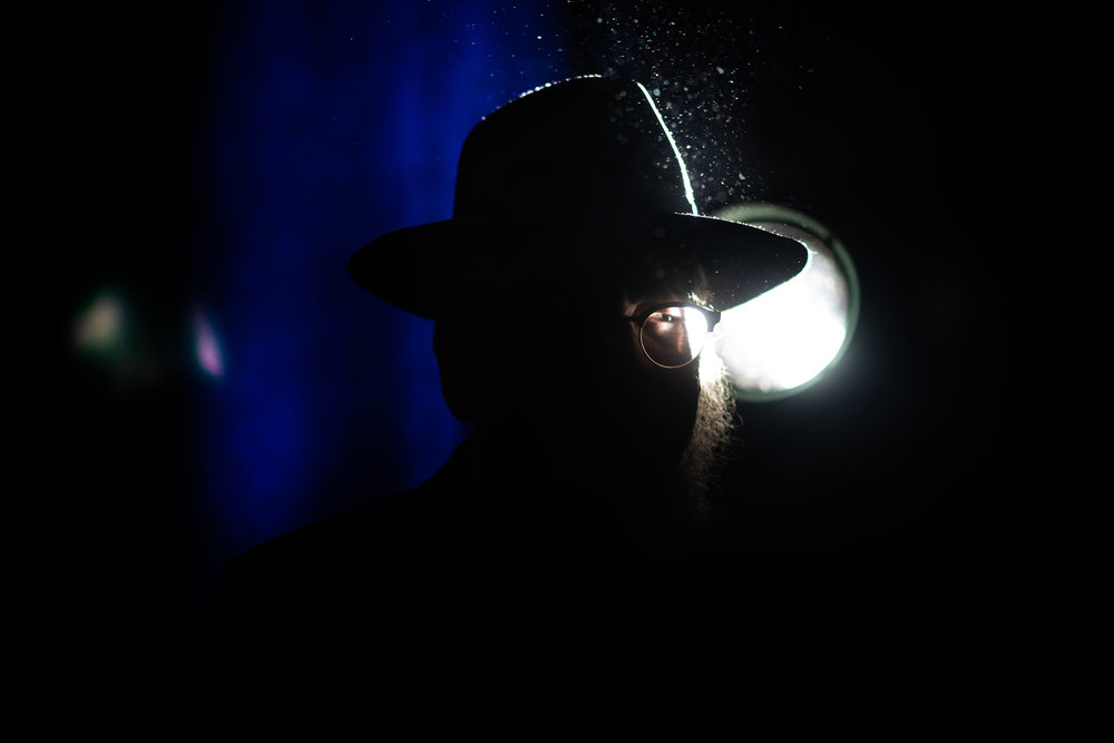 A Chabad-Lubavitch rabbi is silhouetted against a stage light at the end of a banquet in Suffern, NY. Each year, the International Conference of Chabad-Lubavitch Shluchim, or emissaries, takes place in the New York City area for six days.