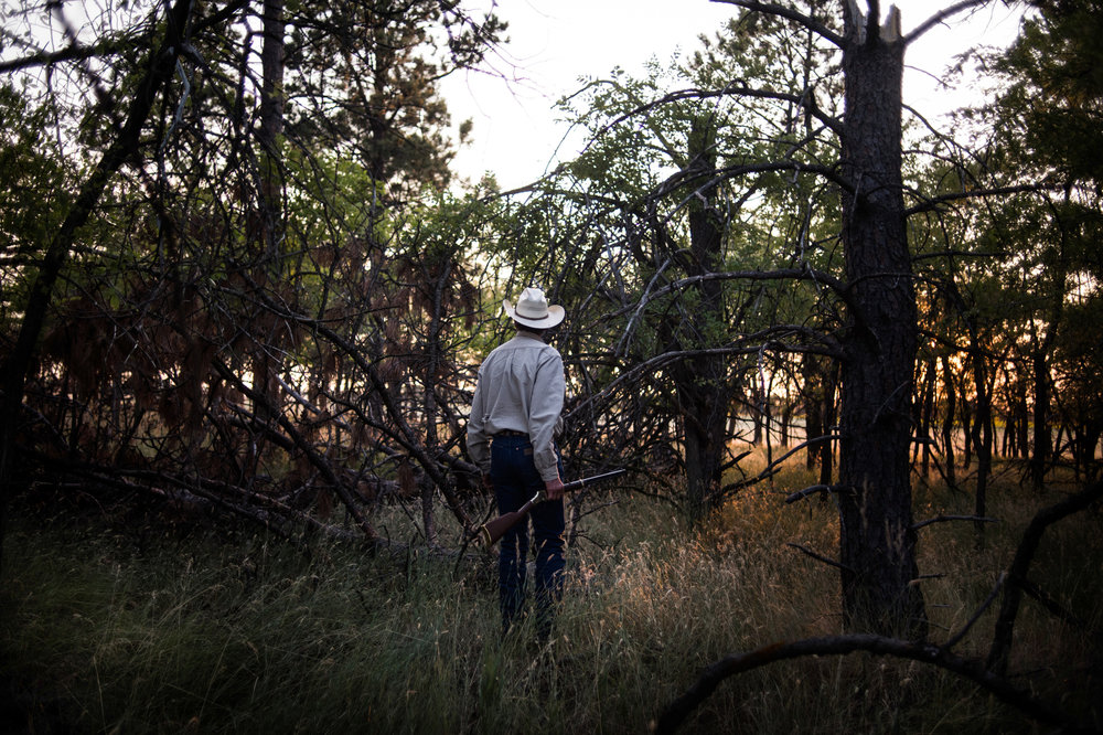 """45°31'54.3""""N 102°15'32.6""""W. 121 miles from the nearest McDonald's.  Kenny Kocer pauses in a clearing of trees as he tracks a skunk he shot on his land in Meadow, SD. Kocer grew up on a local Cheyenne reservation, despite being far below the blood quantum to qualify for membership, and like many in the area holds prejudices against Native Americans."""