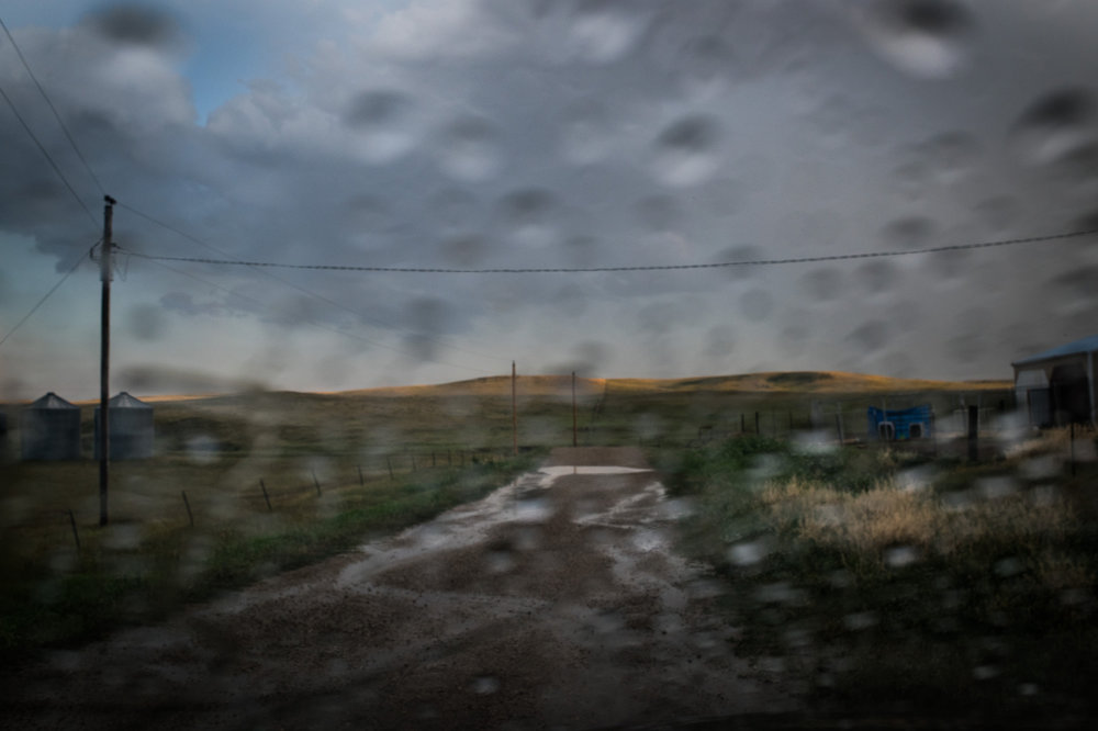 """45°32'45.9""""N 102°07'41.0""""W. 123 miles from the nearest McDonald's.  Rain runs down a dirt road on the Lorius ranch in Meadow, SD on July 28, 2017. An extreme summer drought caused a state of emergency in both North and South Dakota which meant that any small rain was a cause for celebration for ranchers."""