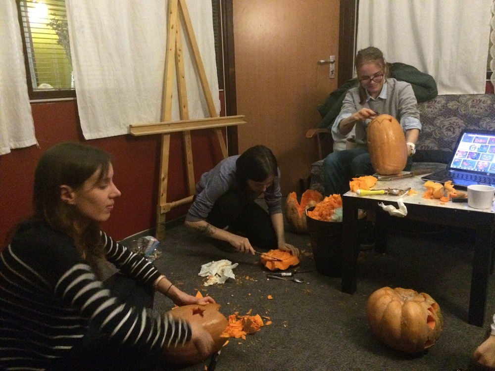 The French club sits around and carves pumpkins.