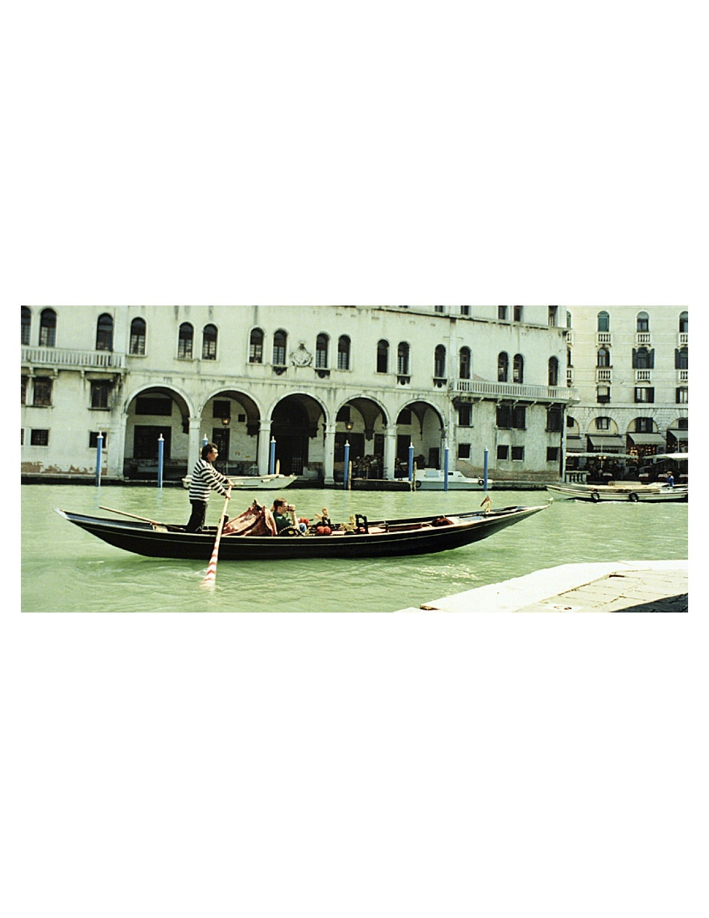 A sandolo (another style of Venetian boat) cruising toward the Rialto Bridge in Venice 2004. Photo by John Synco
