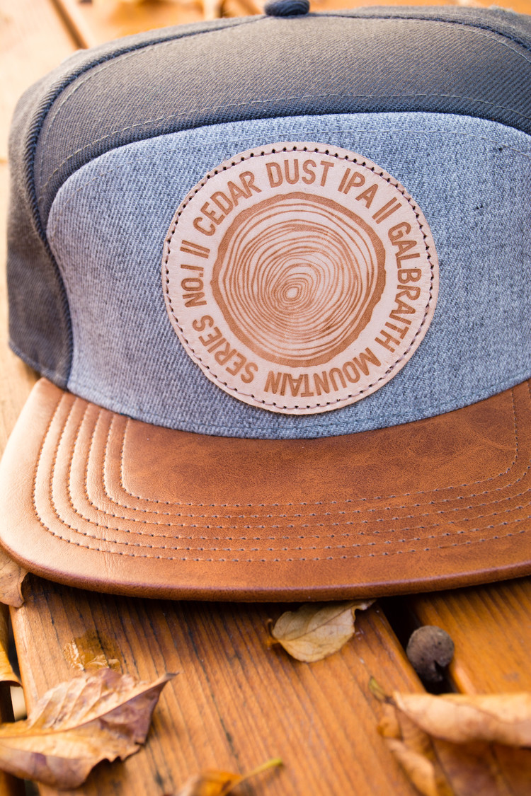 5-Panel Cedar Dust Cap   Custom, one-of-a-kind five-panel Cedar Dust Hat I designed from scratch, materials and all. The cap features a distressed leather bill with two-tone gray panels. I created the cedar dust logo and worked with Blind Alley Leather Co. to create the burned patches. Each hat's patch is a little bit different making it a truly unique piece.  More...