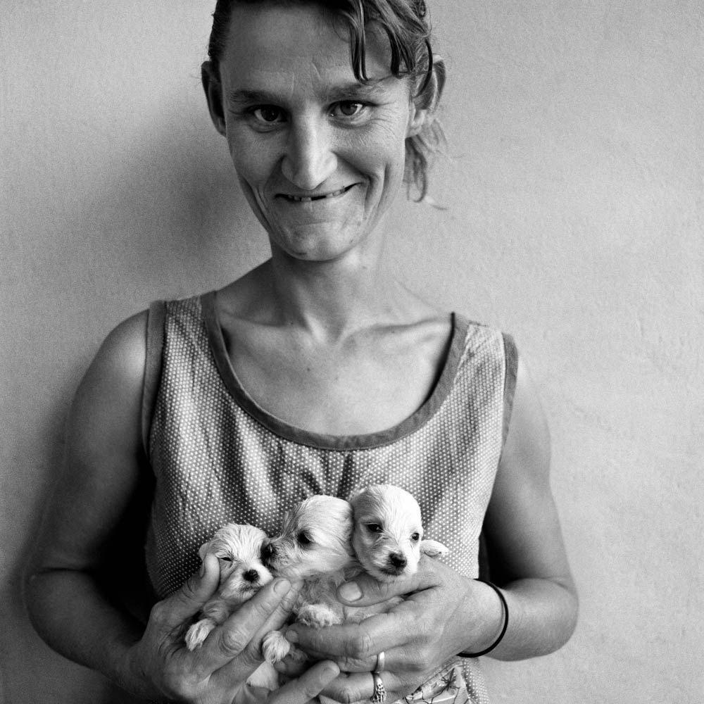 Roger Ballen Wife of Abattoir Worker Holding Three Puppies, Orange Free State - 1994