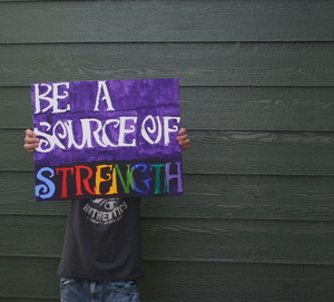 A student poses with a handmade sign for Sources of Strength.