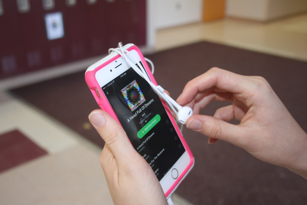 Coldplay's new album plays on a student's phone.