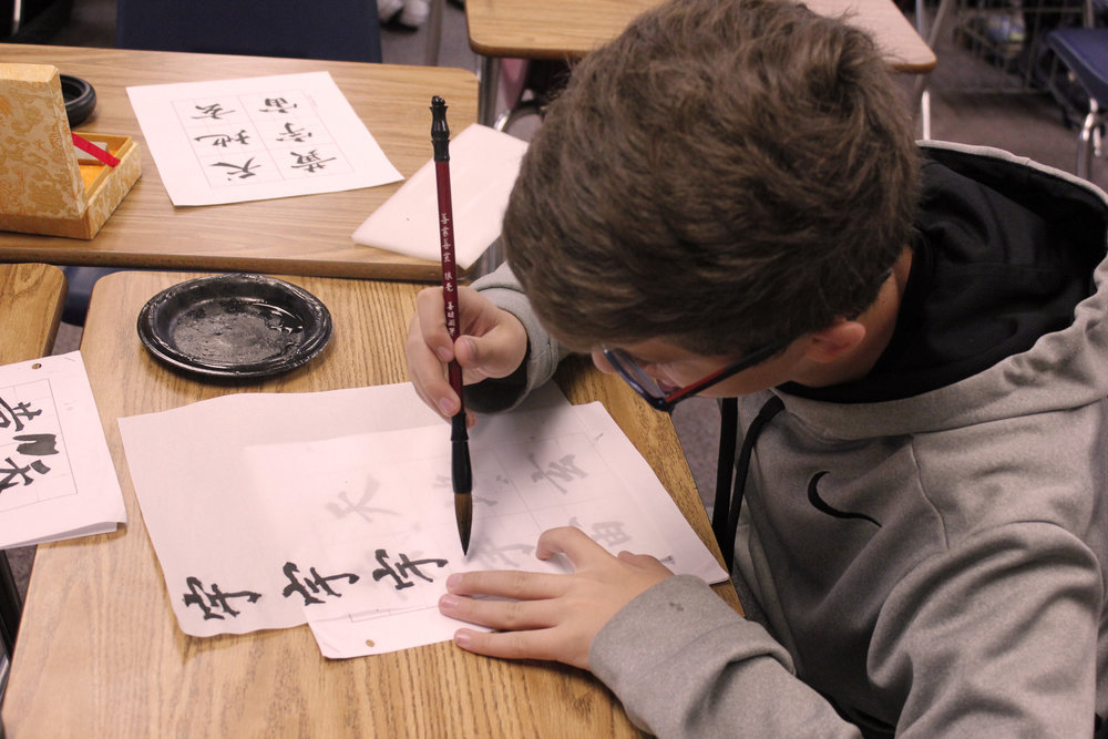 Students practicing writing the Chinese symbols. Photo by Matthew McCarthy